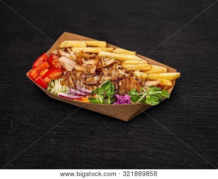 Greek Gyros Dish With French Fries And Vegetables In Paper Plate