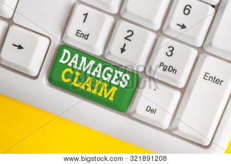 Handwriting text Damages Claim. Concept meaning Deanalysisd Compensation Litigate Insurance File Suit White pc keyboard with empty note paper above white background key copy space. poster