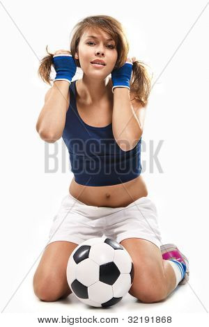 Sexy girl doing fitness, sitting with soccer ball over white background