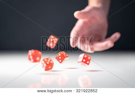 Hand Throwing And Rolling Dice. Gambler Tossing Five Red Poker And Casino Dice On Table. Man Gamblin