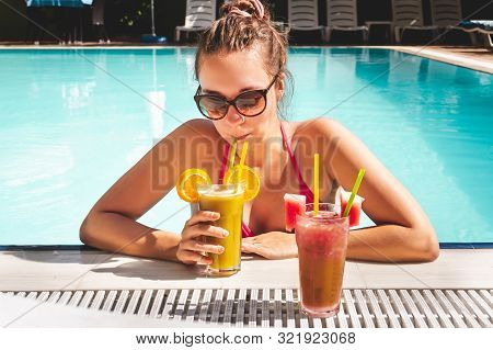 Woman Drinking Cocktail On The Edge Of Swimming Pool In An All Inclusive Hotel Resort Or Luxury Holi