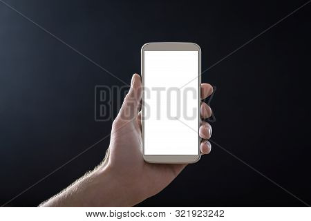 Empty Mobile Phone Screen With Dark Black Background In Shadow At Night. Hand Holding Smartphone Wit