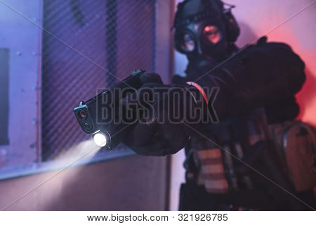 Terrorist With Gas Mask Holding Gun And Aiming A Target In The Hangar