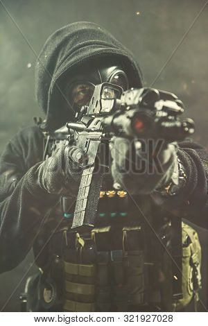 Elite Special Unit Soldier Is Holding Assault Rifle And Aiming At The Target. Studio Photos On A Con