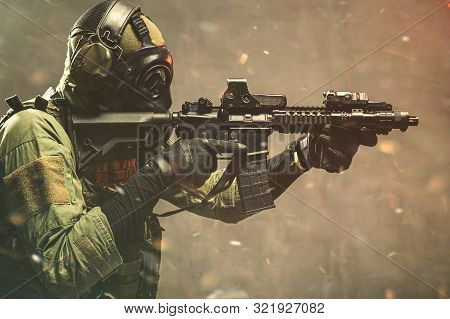 Elite Special Unit Soldier With Gasmask Is Holding Assault Rifle And Aiming At The Target