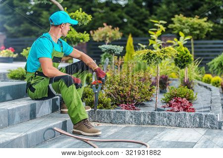 Caucasian Professional Gardener In His 30s And His Newly Developed Residential Garden> Landscaping I