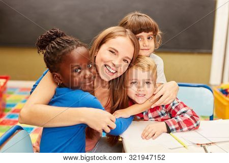 Young woman as a childminder or teacher hugs children in daycare or elementary school
