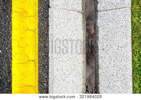 Storm Water Channel Concrete Gutter With Precipitation On The Roadside Of Asphalt Highway With Yello