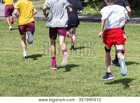 High School Freshmen Boys Running In A Cross Country Race Accross The Grass.