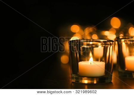 Burning Candle On Table In Darkness, Space For Text. Funeral Symbol