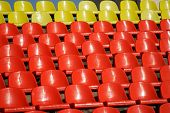 Many red and yellow plastic seats in an open stadium. Free access. Empty seats, without spectators. Waiting for the spectacle. Daylight poster