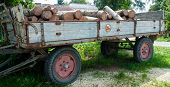 old wooden trailer on farmyard with rusty speed restriction sign and woodpile as cargo poster