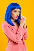 Portrait of an attractive serious funky young girl with blue hair wearing casual outfit standing isolated over yellow background, pretending holding a gun poster