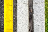 storm water channel concrete gutter with precipitation on the roadside of asphalt highway with yellow markings top view. poster