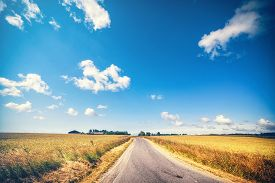 Road Leading To A Farm In The Summer With Wheat Crops Growing In The Sun