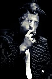 Portrait Of Handsome Gangster Wearing Pinstripe Suit And Looking Through Cigar Smoke At Camera