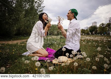 Happy Young Couple In Love On The Grass In Summer Sunny Day. Young Couple Blowing Dandelion On The F