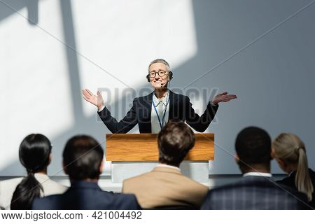 Smiling Lecturer Standing With Open Arms During Conference Near Participants On Blurred Foreground.