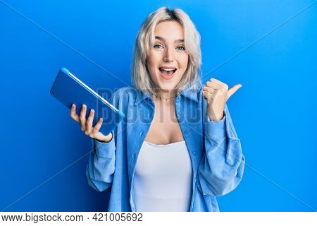 Young blonde girl using touchpad device pointing thumb up to the side smiling happy with open mouth