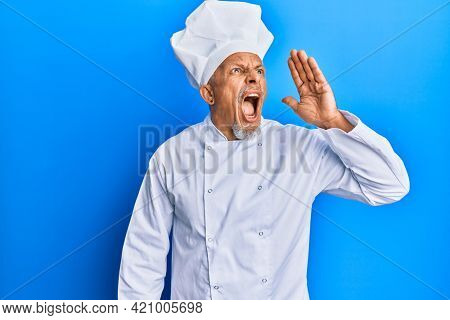 Middle age grey-haired man wearing professional cook uniform and hat shouting and screaming loud to side with hand on mouth. communication concept.
