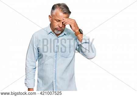 Middle age grey-haired man wearing casual clothes worried and stressed about a problem with hand on forehead, nervous and anxious for crisis