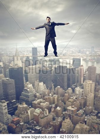 young business man balancing on rope above city
