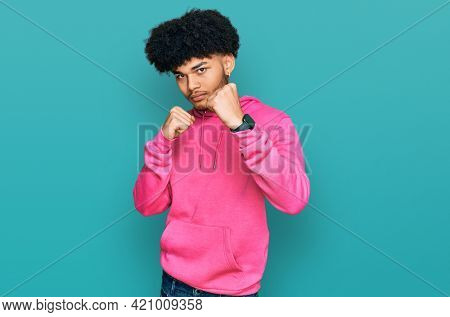 Young african american man with afro hair wearing casual pink sweatshirt ready to fight with fist defense gesture, angry and upset face, afraid of problem