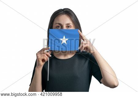 Happy Young White Woman Holding Flag Somalia Flag And Covers Her Face With It Isolated On A White Ba