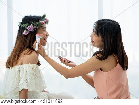 Two Asian Teenagers Making Up Each Other Cheek By Brush On Bed In Bright Bedroom. Concept Teenage Or