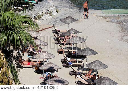 Kusadasi, Turkey - May 2021: Crowd Of People Sunbathing On A Beach, Top View. Tourists In Lounge C