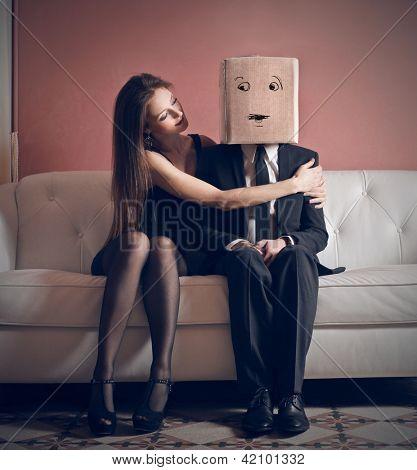 hermosa mujer abraza a hombre elegante con la caja en la cabeza, sentada en el sofá
