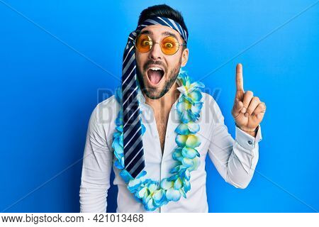 Young hispanic businessman wearing party funny style with tie on head pointing finger up with successful idea. exited and happy. number one.