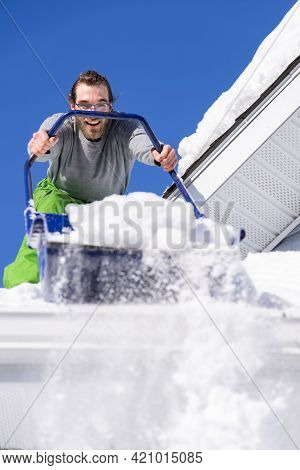 Close Up Shot From Below Of A Young Man Posing With A Blue Manual Shovel From The Roof Of A House Wh