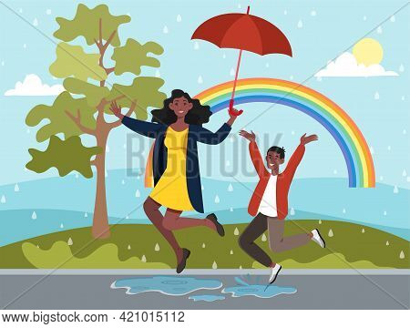 Happy Mother Is Jumping In A Puddle With Her Little Son. Mother And Child Are Having Fun Outdoors Wi