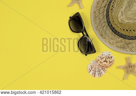 Summer Background. Straw Sun Hat, Sunglasses And Seashells On A Yellow Background. Top View, Close-u