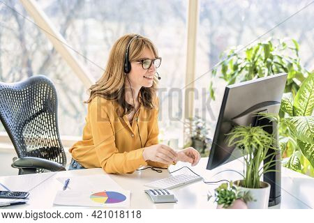 Mature Businesswoman In Headset Speaking By Conference Call While Looking At Computer. Home Office.