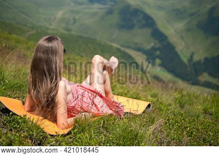 Young Woman In Red Dress Lying Down On Green Grassy Field Resting On A Sunny Day In Summer Mountains