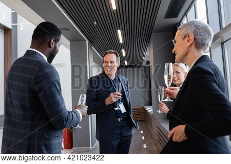 Multiethnic Business Colleagues Holding Champagne Glasses During Conversation On Symposium.