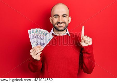 Young bald man holding egyptian pounds banknotes smiling with an idea or question pointing finger with happy face, number one