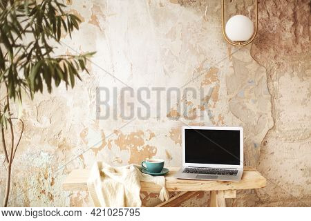 Retro Cup Of Fresh Coffee Placed On Knitwear Near Modern Netbook With Blank Screen On Wooden Table A