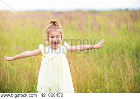 The Girl Runs Into The Field With Her Arms Outstretched Like An Airplane. Carefree Childhood, Summer