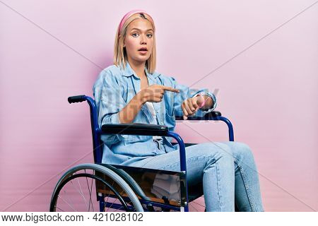 Beautiful blonde woman sitting on wheelchair in hurry pointing to watch time, impatience, upset and angry for deadline delay