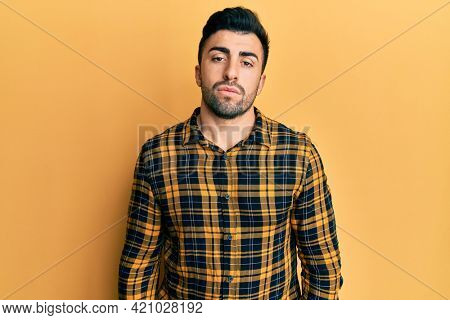 Young hispanic man wearing casual clothes looking sleepy and tired, exhausted for fatigue and hangover, lazy eyes in the morning.