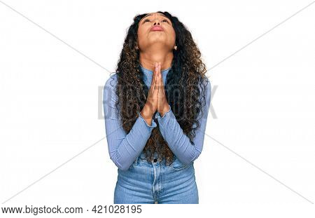 Young hispanic woman with curly hair wearing casual clothes begging and praying with hands together with hope expression on face very emotional and worried. begging.
