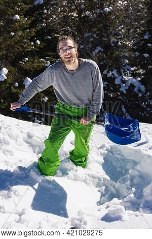 Full Figure Portrait From Above Of A Young Man Knee Deep In The Fresh Snow On A Roof, Posing For Cam