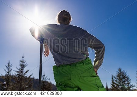 View From Behind Of A Young Man Leaning On The Handle Of A Blue Snow Shovel While Taking A Break Dur