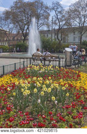 Graz, Austria-april 25, 2021: People Relaxing Near The Fountain In Jakominiplatz Square In The City