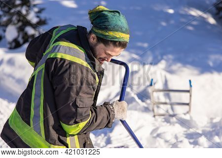 Young Man In Fluo Visibility Clothes And Blue Manual Shovel Removing Knee Deep Fresh Snow From A Cou