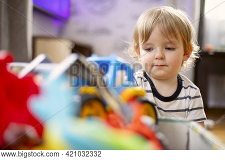 A Huge Bunch Of Different And Colored Toys In Front Of Playful Child. Little Kid Is Playing Toys In
