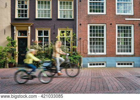 Motion blurred bicycle rider cyclist woman and child on bicycle very popular means of transport in Netherlands in street with old houses of Delft, Netherlands